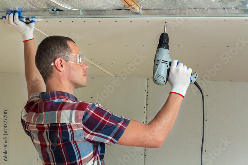 Young man in goggles fixing drywall suspended ceiling to