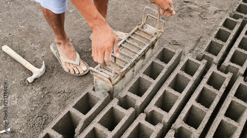 Fotografie, Obraz  Man manually produces brick molds for construction from volcanic ash in the city of Legazpi