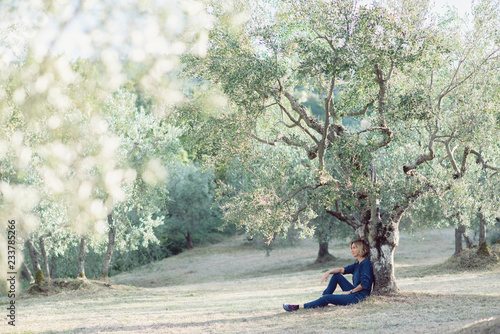 Fotomural Romantic young beautiful girl with blond fair hair in blue jeans sitting under olive tree in garden