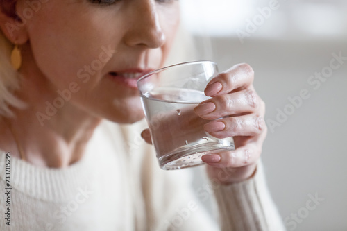 Foto Aged woman holding glass feeling thirsty or dehydrated, senior female drinking fresh pure aqua following healthy lifestyle, elderly lady having still mineral water