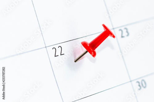 Fotografia  Close up number 22 day marked with red thumbtack on calendar