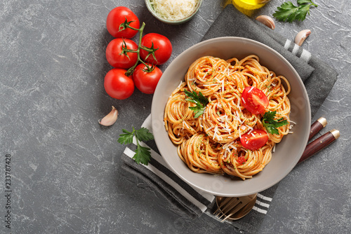 Pasta, spaghetti with tomato sauce in gray bowl on grey background Fototapeta
