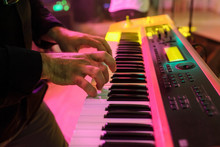 Close Up Of Young Musician Man Hands Plays On Electric Piano Keys In His Performance On Stage Of A Wedding Banquet Hall In Yellow, Pink And Greend Lights