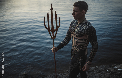 Fotografie, Tablou  A young man with a trident against the background of water.