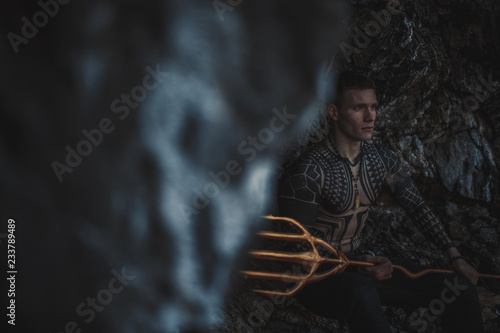 Fotografie, Tablou  A young man with a trident in his hands against the background of rocks