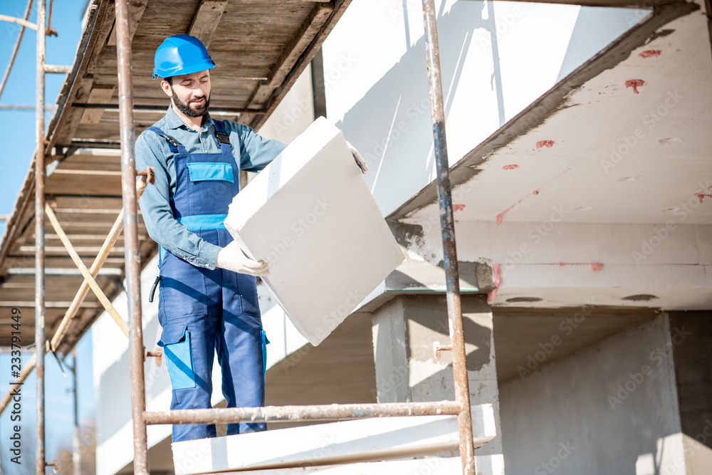 Fototapeta Builder warming a building facade with foam panels standing on the scaffoldings on the construction site