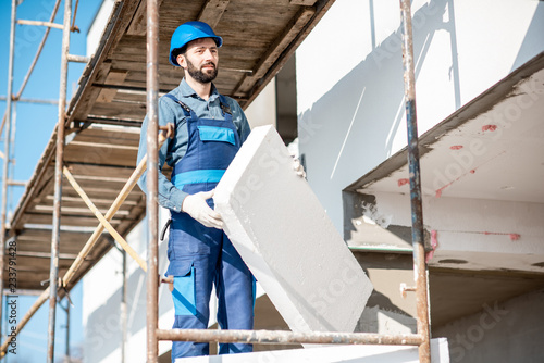 Photographie Builder warming a building facade with foam panels standing on the scaffoldings