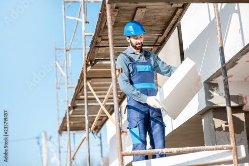 Obraz Builder warming a building facade with foam panels standing on the scaffoldings on the construction site - fototapety do salonu