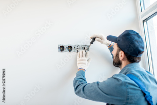 Electrician in uniform mounting electric sockets on the white wall indoors Canvas Print
