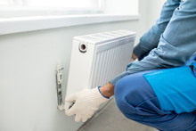 Workman Mounting Water Heating Radiator On The White Wall Indoors, Close-up View