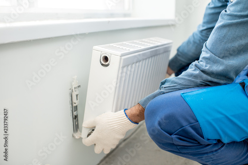 Fototapeta Workman mounting water heating radiator on the white wall indoors, close-up view obraz