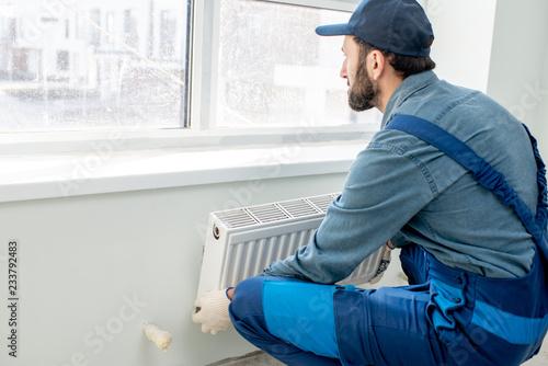 Cuadros en Lienzo Workman mounting water heating radiator near the window in the white renovated l