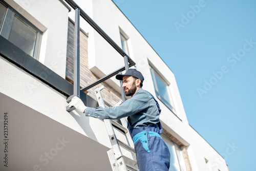 Builder in blue uniform mounting aluminium fence on the balcony of the new build Fototapet