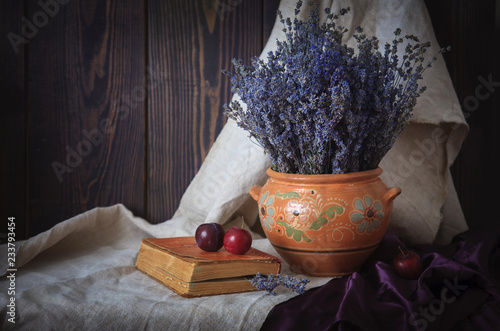 Photo  Still life with a bouquet of lavender, a book and plums on the table