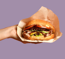 Woman Hands Hold Big Cheese Burger Barbeque Sandwich With Marble Beef On Purple