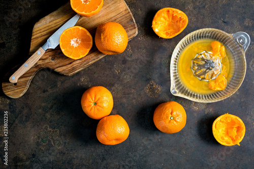 Overhead view of oranges and juicer on table