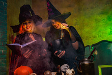 Portrait Of Smiling Two Witches In Black Hats Reading Book At Table With Pumpkin And Skulls