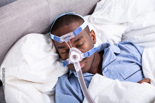 Photo Man Wearing CPAP Mask Sleeping On Bed