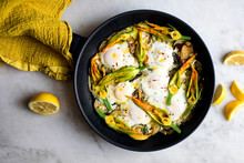 Overhead View Of Braised Eggs With Courgettes Flowers, Feta And Lemon