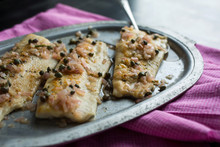 Close Up Of Pan Fried Trout With Rosemary, Lemon And Capers