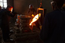 Workers Pouring Molten Metal From Flasks Into Moulds