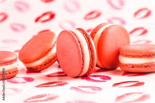 Poster Macarons French red macarons close up spilled on white background with red kisses arrangement front view in studio