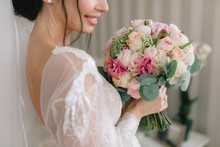 Bride In Beautiful Dress Is A Smiling And Holds A Wedding Bouquet.