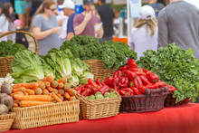 People Enjoy The Morning Outdoors At The Local Green Farmers Market. Lots Of Fresh Produce Of Many Verity Of Vegetables.