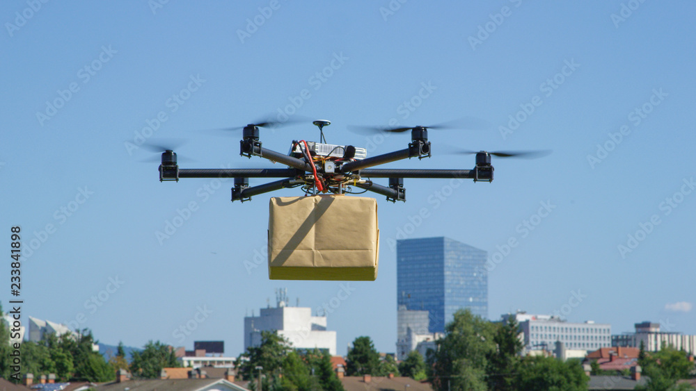 Fototapeta CLOSE UP: UAV drone delivery delivering big brown post package into urban city
