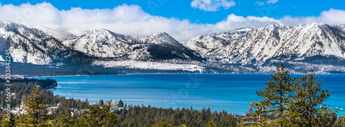 Fotobehang Bergen Panoramic view towards Lake Tahoe on a sunny clear day; the snow covered Sierra mountains in the background; evergreen forests in the foreground