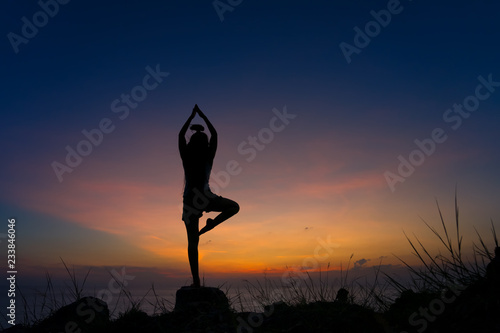 Fotografie, Obraz  Silhouette of woman practicing warrior one pose yoga on the beach at sunset