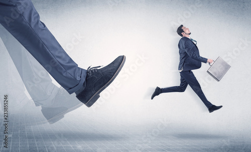 Fotografie, Obraz  Businessman big foot kicking small, young businessman who is flying