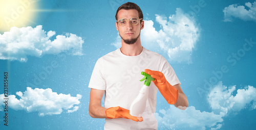 Fotografia  Sunny and cloudy concept with male housekeeper and orange gloves on his hand