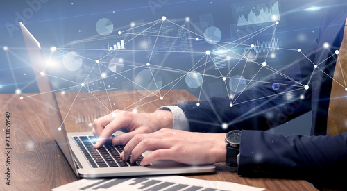 Businessman typing on laptop with linked reports charts grapghs around Fototapeta