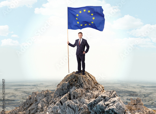 Photo Successful businessman on the top of a mountain holding victory flag