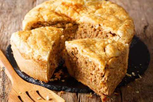 Snack rustic tourtiere pie with pork, mashed potatoes and spices close-up. horizontal