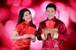Leinwanddruck Bild - Happy couple holds envelope in the studio