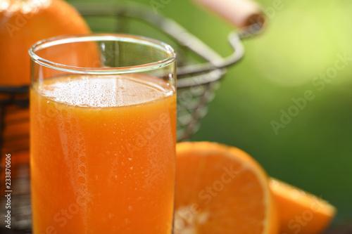 Fresh orange juice in glass with sliced orange on nature background