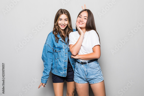 9e8f39dbf Portrait of two cheerful mixed race young women standing together ...