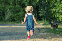 Little Girl, Dressed On Dungarees  Is Chasing A Hen On A Country Road