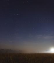 Moon Setting In A Misty Field On A Starry Night