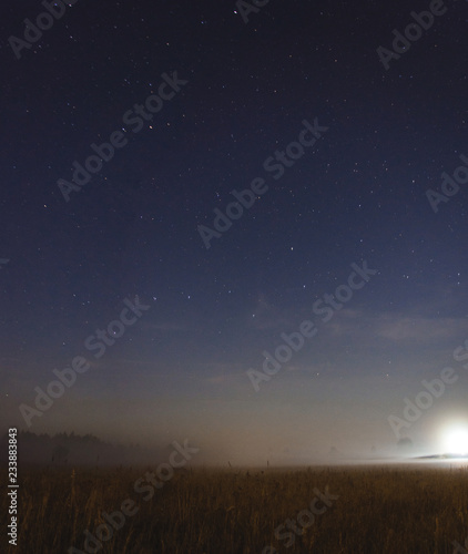 Photo Moon setting in a misty field on a starry night