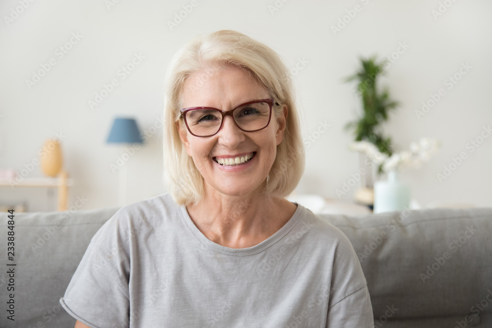 Fototapeta Smiling middle aged mature grey haired woman looking at camera, happy old lady in glasses posing at home indoor, positive single senior retired female sitting on sofa in living room headshot portrait