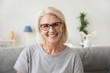 canvas print picture - Smiling middle aged mature grey haired woman looking at camera, happy old lady in glasses posing at home indoor, positive single senior retired female sitting on sofa in living room headshot portrait
