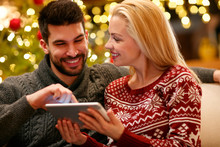 Couple In Warm Sweaters Enjoying With Tablet On Christmas .