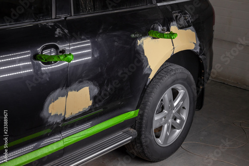 Fotografía Repair of car body parts in black after an accident and scratches by applying a