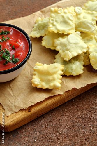 deliziosi ravioli fritti con salsa di pomodoro su sfondo tavolo di ...