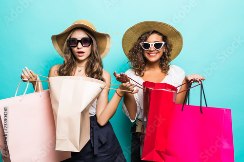 Foto  Portrait of two young sexy stylish smiling brunette women holding shopping bags