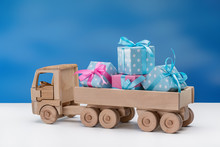 Wooden Toy Truck With Gifts In Elegant Boxes In  Back.
