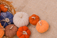 Beautiful And Cozy Knitted Woolen Pumpkins Spill Out Of The Basket - The Perfect Autumn And Halloween Decoration On The Sackcloth Background.  Copy Space.